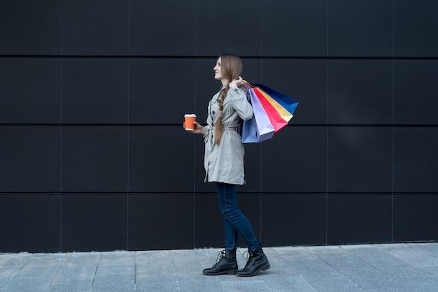 Szczęśliwa młoda kobieta z kolorowymi torbami i papierową filiżanką.