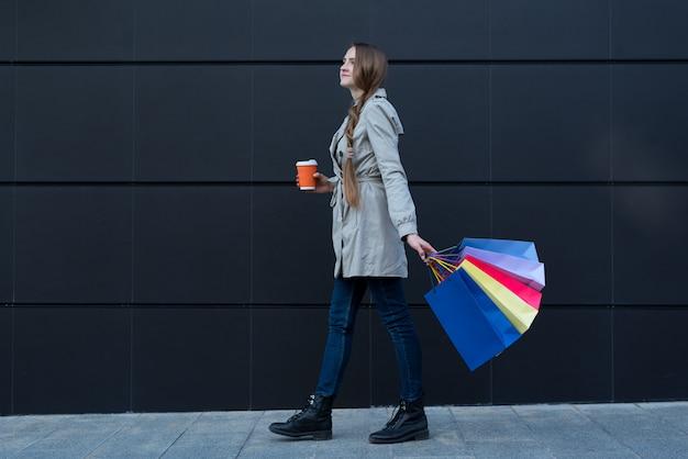 Szczęśliwa młoda kobieta z kolorowymi torbami i papierowej filiżanki odprowadzeniem na ulicie.
