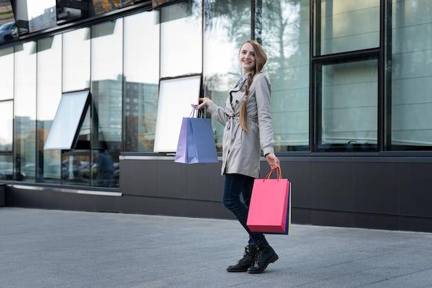 Szczęśliwa młoda kobieta z kolorowymi torbami zbliża centrum handlowe. zakupoholiczka