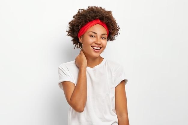Szczęśliwa młoda kobieta z kręconymi włosami, dotyka szyi, cieszy się przyjemnymi chwilami w życiu, ubrana w ubranie