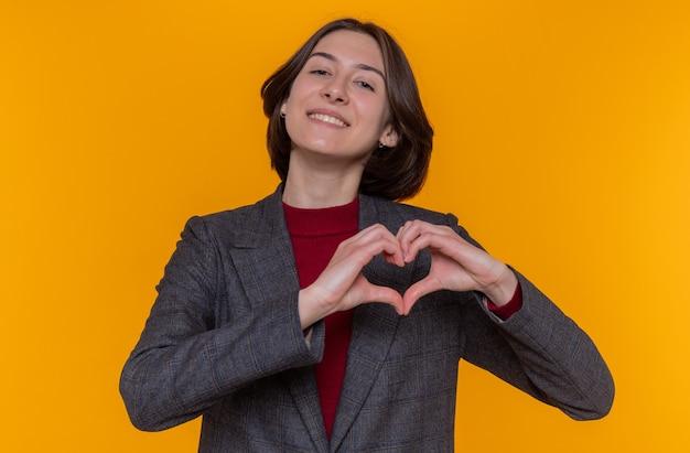 Szczęśliwa młoda kobieta z krótkimi włosami na sobie szarą kurtkę