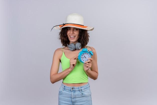 Szczęśliwa młoda kobieta z krótkimi włosami w zielonej bluzce na sobie kapelusz przeciwsłoneczny trzyma niebieski budzik na białym tle