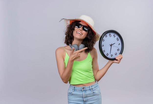 Szczęśliwa młoda kobieta z krótkimi włosami w zielonym crop top w okularach przeciwsłonecznych i kapeluszu słonecznym, wskazując na zegar ścienny na białym tle