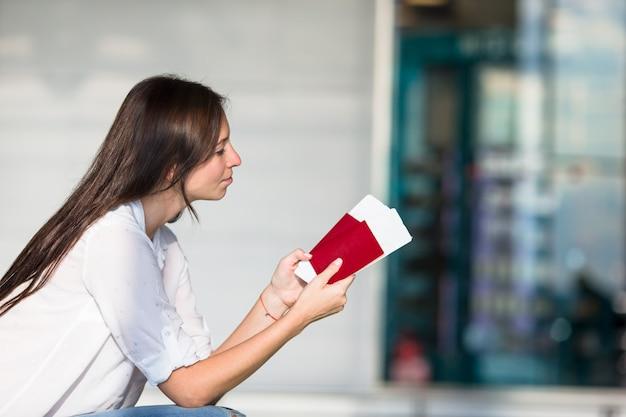 Szczęśliwa młoda kobieta z lotniczym biletem i paszportami przy lotniskowym czekaniem lot