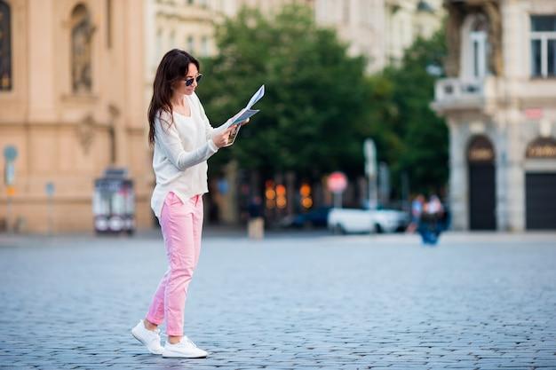 Szczęśliwa młoda kobieta z mapa miasta w mieście. podróżuje turystycznej kobiety z mapą w praga outdoors podczas wakacji w europa.