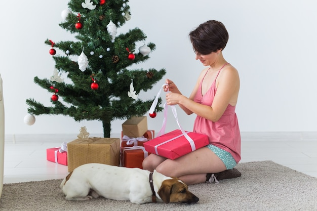 Szczęśliwa młoda kobieta z pięknym psem otwierającym pudełko pod choinką