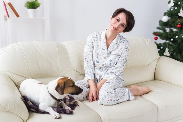Szczęśliwa młoda kobieta z pięknym psem w salonie