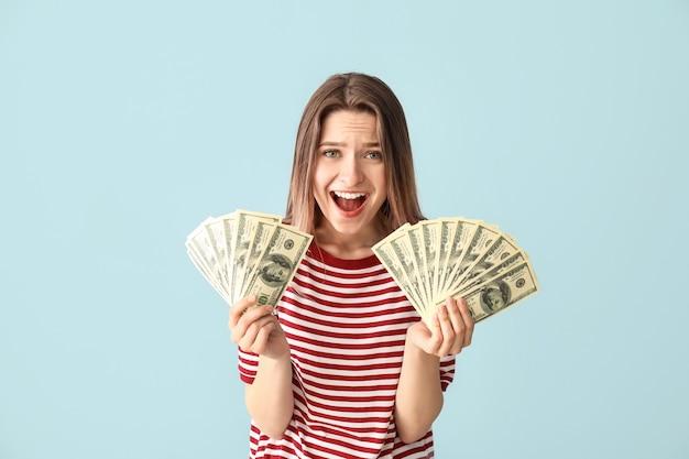 Szczęśliwa młoda kobieta z pieniędzmi na niebiesko