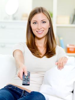 Szczęśliwa młoda kobieta z pilotem, siedząc na kanapie i oglądając telewizję