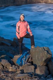 Szczęśliwa młoda kobieta z plecakiem ono uśmiecha się przy jeziorem
