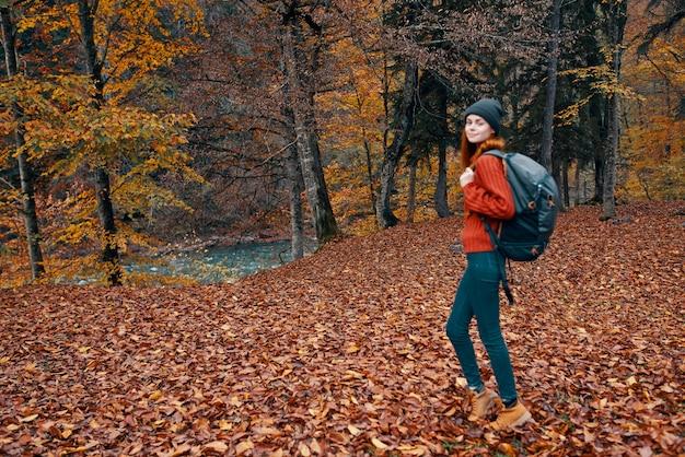 Szczęśliwa młoda kobieta z plecakiem w dżinsach i swetrze spaceruje po lesie jesienią w pobliżu