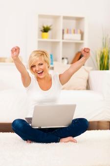 Szczęśliwa młoda kobieta z podniesionymi rękami