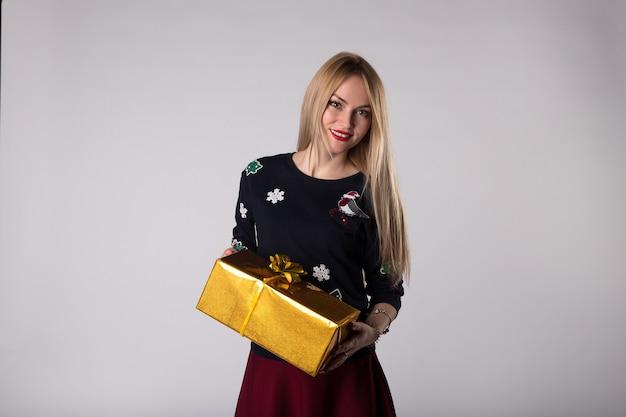Szczęśliwa młoda kobieta z pudełkiem na prezent