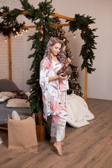 Szczęśliwa młoda kobieta z pudełkiem prezentowym podczas przygotowań do bożego narodzenia w domu