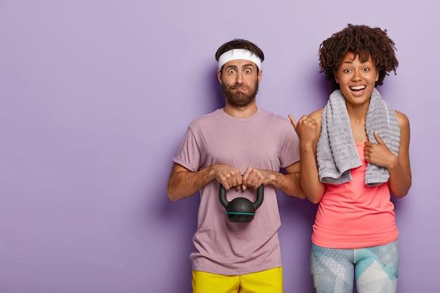 Szczęśliwa młoda kobieta z ręcznikiem na ramionach wskazuje na męża, który jest zaskoczony wyrazem twarzy