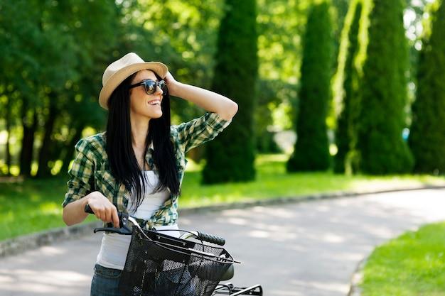 Szczęśliwa młoda kobieta z rowerem