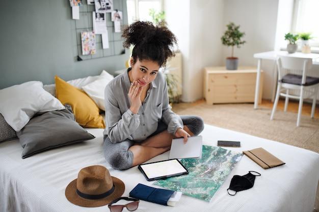 Szczęśliwa młoda kobieta z tabletem i mapą w pomieszczeniu w domu, planowanie podróży.