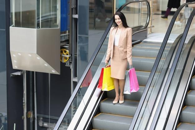 Szczęśliwa młoda kobieta z zakupami schodzi po schodach ruchomych w centrum handlowym po zakupach