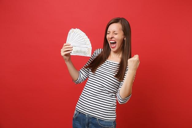 Szczęśliwa młoda kobieta z zamkniętymi oczami krzyczy, robi gest zwycięzcy, trzymając pakiet wiele dolarów gotówki na białym tle na czerwonym tle. koncepcja życia szczere emocje ludzi. makieta miejsca na kopię.