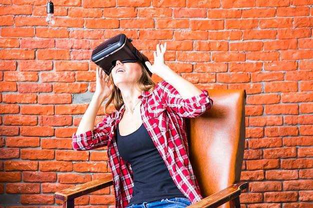 Szczęśliwa młoda kobieta z zestawem słuchawkowym wirtualnej rzeczywistości lub okularami 3d i słuchawkami