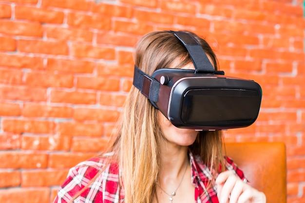 Szczęśliwa młoda kobieta z zestawem słuchawkowym wirtualnej rzeczywistości lub okularami 3dd