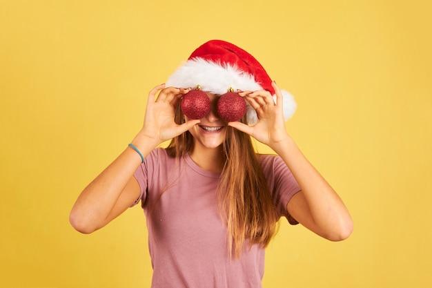 Szczęśliwa młoda kobieta za pomocą czerwonych bombek jako okularów i na sobie kapelusz świętego mikołaja na żółto