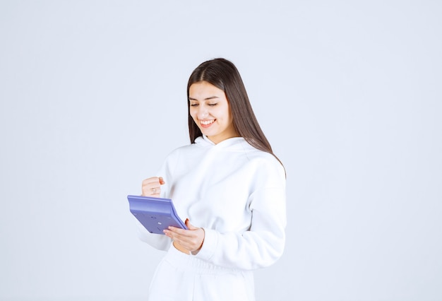 Szczęśliwa młoda kobieta za pomocą kalkulatora na biało szarym tle.