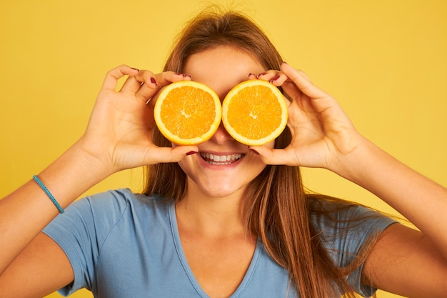 Szczęśliwa młoda kobieta za pomocą pomarańczy jako okularów na żółto