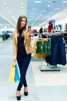 Szczęśliwa młoda kobieta za pomocą smartfona w centrum handlowym