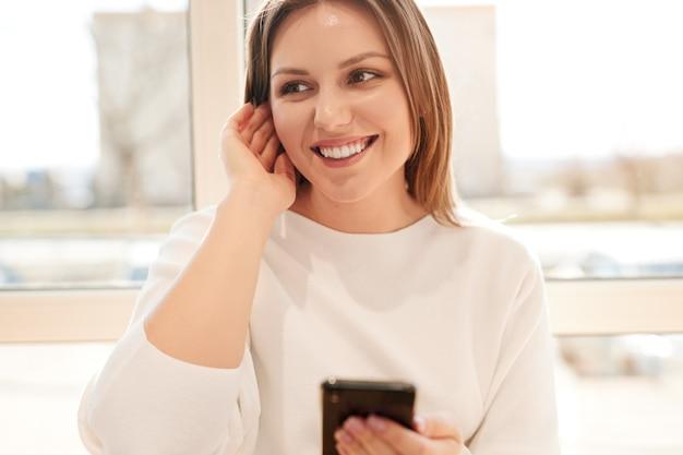 Szczęśliwa młoda kobieta za pomocą smartfona w pobliżu okna
