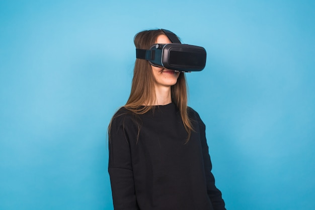 Szczęśliwa młoda kobieta za pomocą zestawu słuchawkowego wirtualnej rzeczywistości na niebiesko