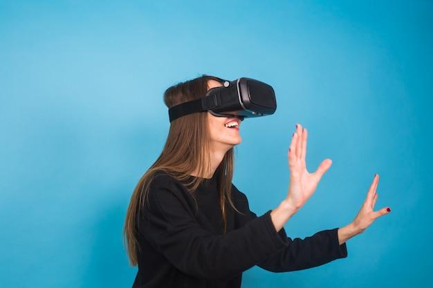 Szczęśliwa młoda kobieta za pomocą zestawu słuchawkowego wirtualnej rzeczywistości.