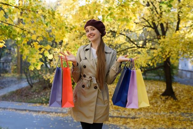 Szczęśliwa młoda kobieta zakupoholiczka z kolorowymi torbami zbliża centrum handlowe.