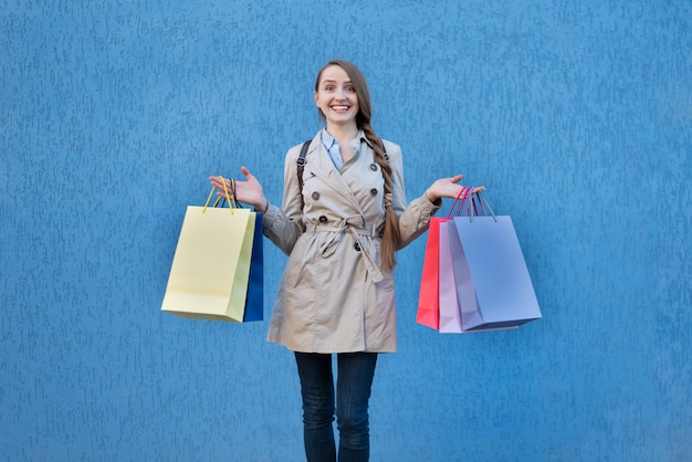 Szczęśliwa młoda kobieta zakupoholiczka z kolorowymi torbami.