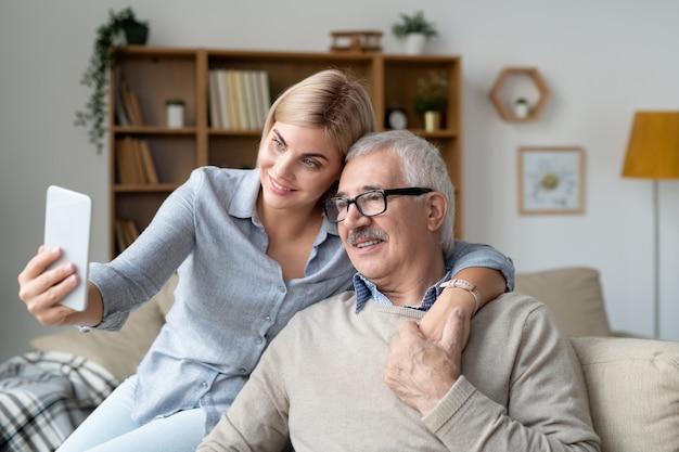 Szczęśliwa młoda kobieta ze smartfonem obejmując swojego starszego ojca, siedząc na kanapie i robiąc selfie w środowisku domowym
