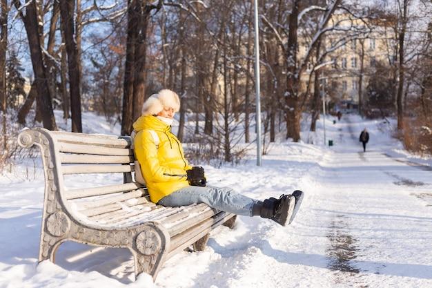 Szczęśliwa Młoda Kobieta Zimą W Ciepłych Ubraniach W Zaśnieżonym Parku W Słoneczny Dzień Siedzi Na ławkach I Sama Cieszy Się świeżym Powietrzem I Kawą Darmowe Zdjęcia