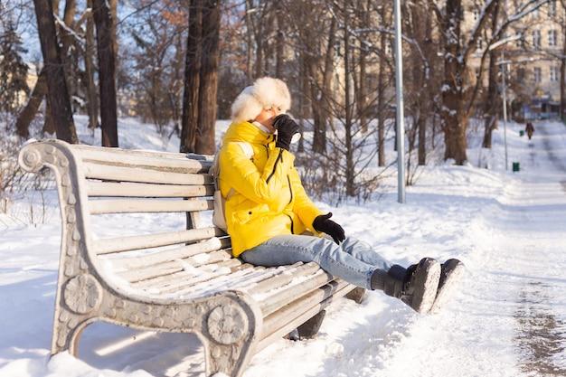 Szczęśliwa młoda kobieta zimą w ciepłych ubraniach w zaśnieżonym parku w słoneczny dzień siedzi na ławkach i sama cieszy się świeżym powietrzem i kawą