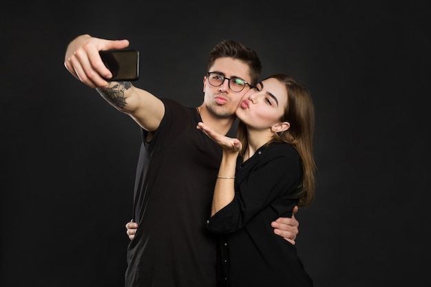 Szczęśliwa młoda kochająca para robi selfie i ono uśmiecha się podczas gdy stojący przeciw czerni ścianie