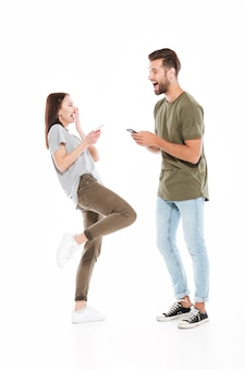 Szczęśliwa młoda kochająca para trzyma telefony.