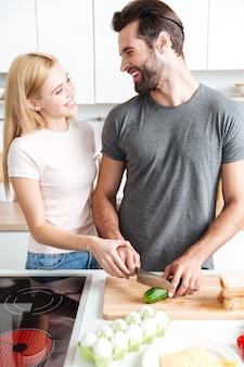 Szczęśliwa młoda kochająca pary pozycja przy kuchnią i kucharstwem