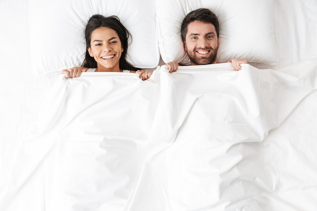 Szczęśliwa młoda, kochająca się para leży w łóżku, chowając się pod kocem
