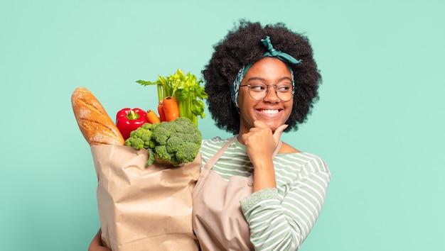 Szczęśliwa młoda ładna afro kobieta trzyma worek warzyw