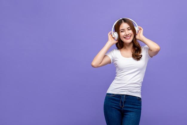 Szczęśliwa młoda ładna azjatycka kobieta słucha muzyka obok kopii przestrzeni