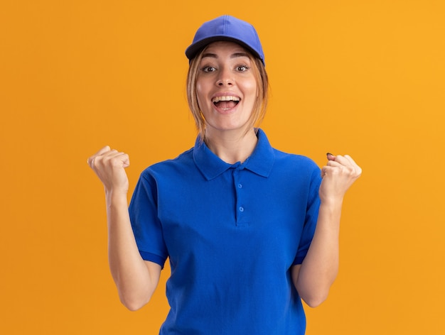 Szczęśliwa młoda ładna dziewczyna dostawy w mundurze trzyma pięści na pomarańczowo