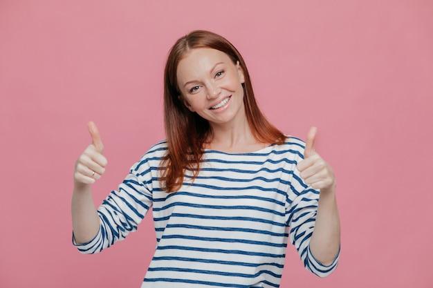 Szczęśliwa młoda ładna europejska dama daje podwójny kciuk, lubi komuś pomysł lub wyraża aprobatę