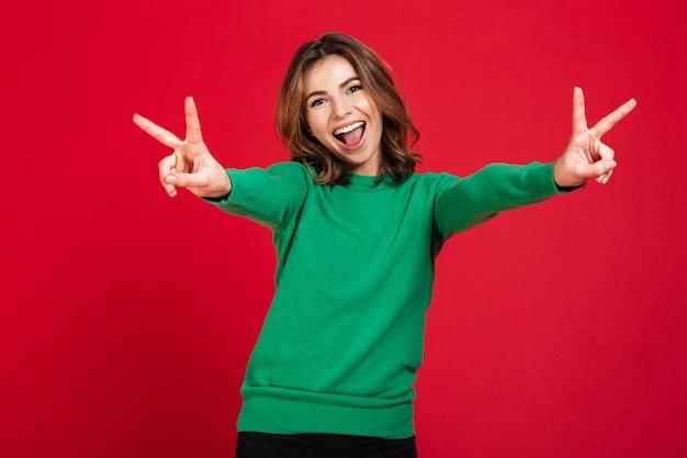 Szczęśliwa młoda ładna kobieta pokazuje pokoju gest.