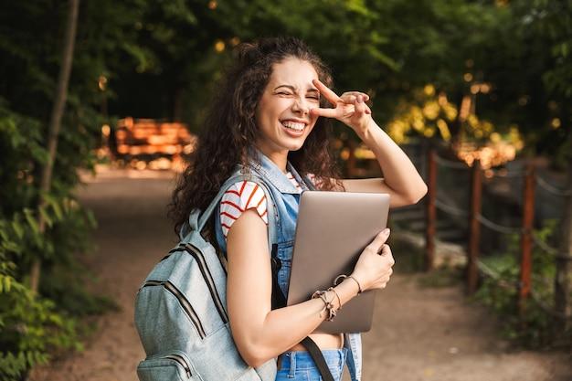 Szczęśliwa młoda ładna kobieta trzyma laptop