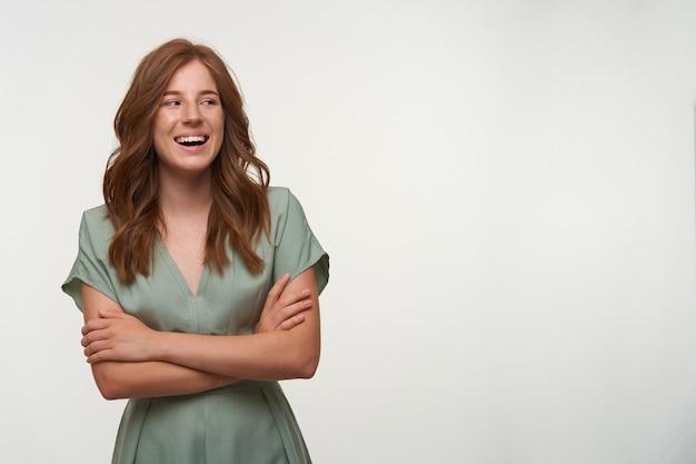 Szczęśliwa młoda ładna kobieta z rudymi włosami pozuje ze skrzyżowanymi rękami, patrząc na bok z szerokim i szczerym uśmiechem, ubrana w sukienkę vintage w pastelowym kolorze