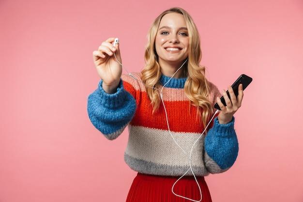 Szczęśliwa młoda ładna piękna kobieta pozuje odizolowana na różowej ścianie za pomocą telefonu komórkowego, słuchając muzyki, daje ci słuchawkę
