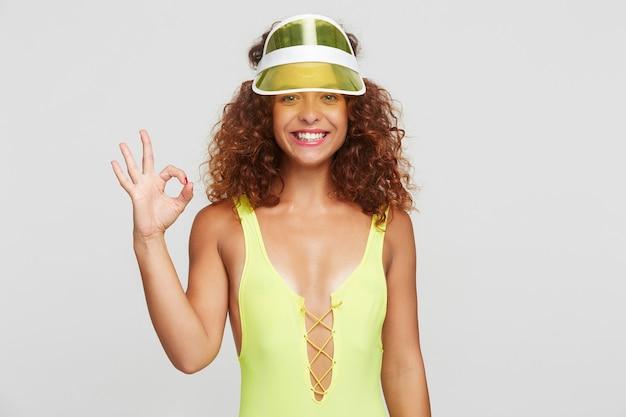 Szczęśliwa młoda ładna rudowłosa kręcona kobieta z naturalnym makijażem podnosząca rękę z dobrze wykonanym gestem i uśmiechająca się radośnie do kamery, pozując na białym tle